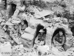 Men of the Border Regiment resting in shallow dugouts near Thiepval Wood during the Battle of the Somme during August 1916. (IWMQ872)