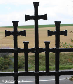 Feature with the five crosses on the metal entrance gate into Fricourt military cemetery on the Somme.